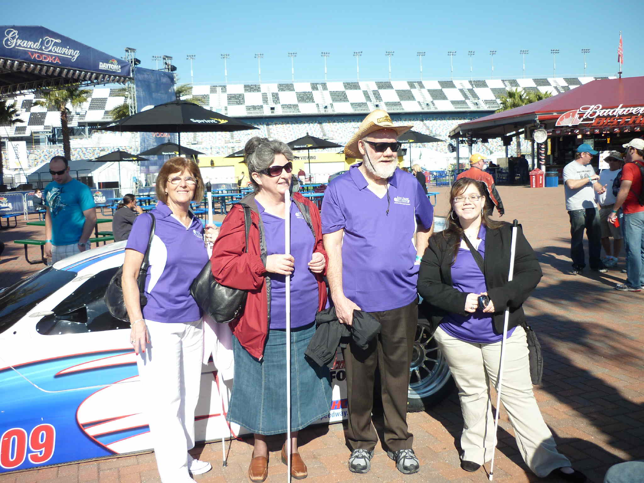Pamela and John Glisson, Angela Dehart and Cathy Jackson standing in front of a race car at the race track