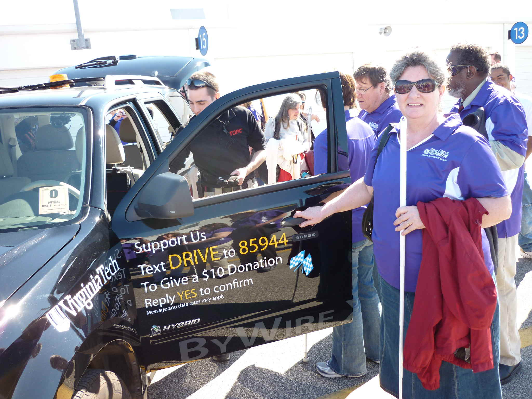 Pamela Glisson holding the door of an SUV challenge vehicle