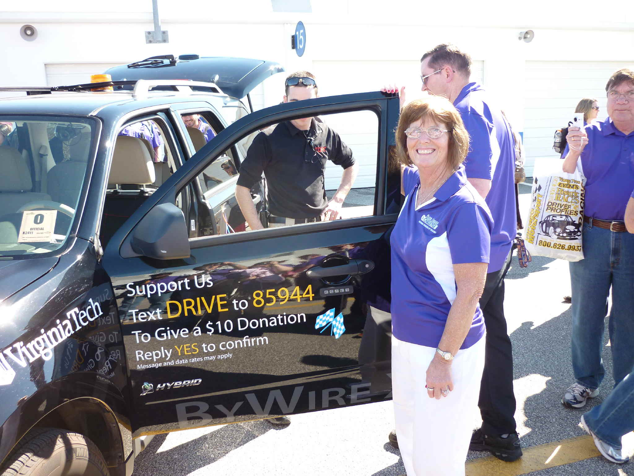Cathy Jackson holding the door of an SUV challenge vehicle